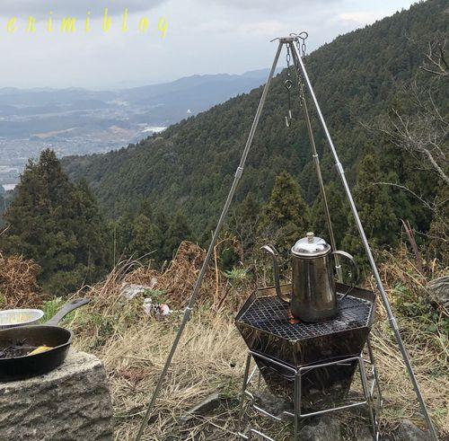 キャンプ場で使用中の焚き火台とポットと三脚