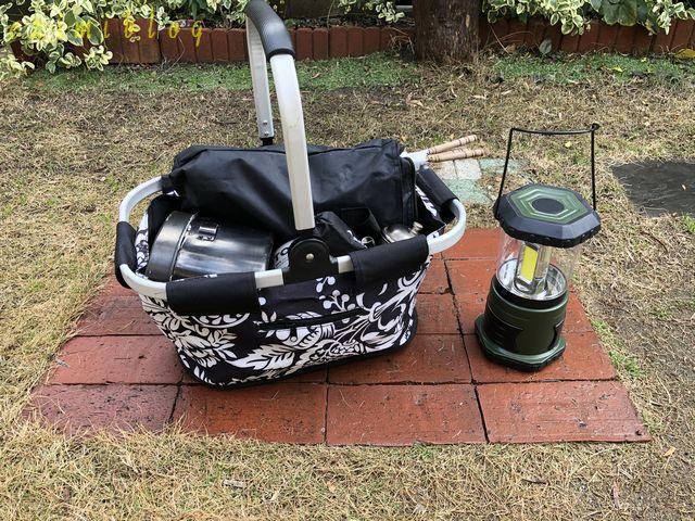 手提げカゴに入ったバーベキューの道具とランタン